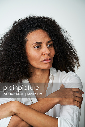Black curly haired woman with arms crossed looking away - p300m2264590 by Annika List