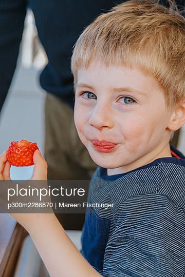 Portrait of boy with strawberry, Viersen, NRW, Germany - p300m2286870 von Mareen Fischinger