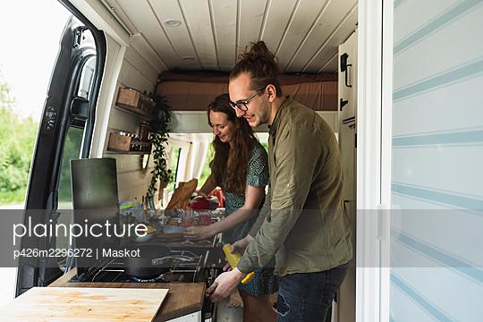 Heterosexual couple preparing food in camping van during vacation - p426m2296272 by Maskot