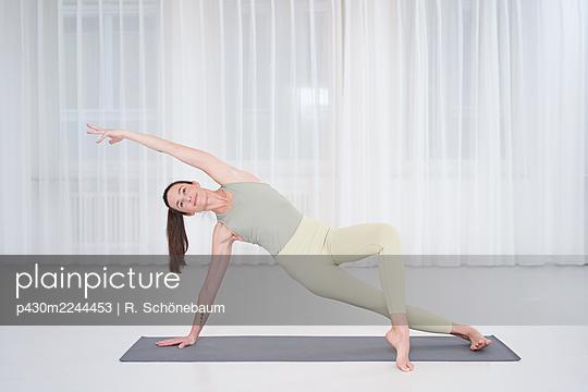 Woman practicing yoga in gym - p430m2244453 by R. Schönebaum
