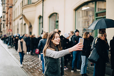 Smiling girl taking selfie through smart phone against crowd in city - p426m1555868 by Maskot
