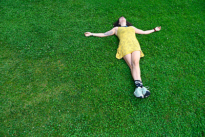 Woman lies on grass with arms outstretched - p427m2206482 by Ralf Mohr