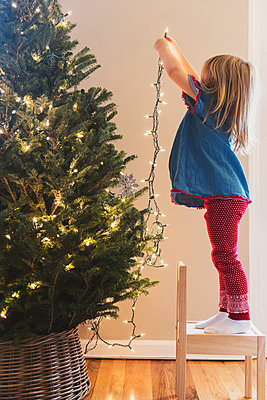 Caucasian girl hanging lights on Christmas tree - p555m1231860 by JGI/Jamie Grill