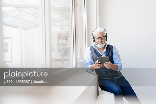 Mature man with tablet and headphones at the window - p300m1505387 by Joseffson