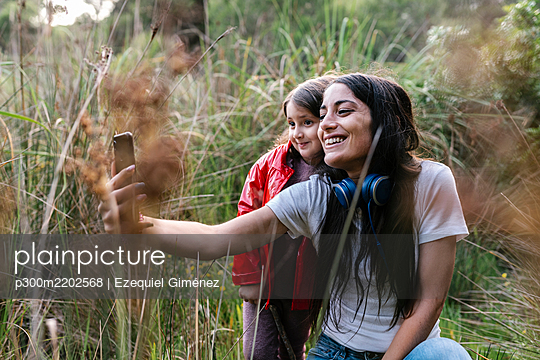 Mother and daughter taking a selfie in the woods - p300m2202568 by Ezequiel Giménez