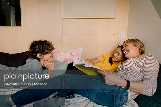 Smiling boy looking at cheerful mother and sister with book while lying on bed - p426m2279698 by Maskot