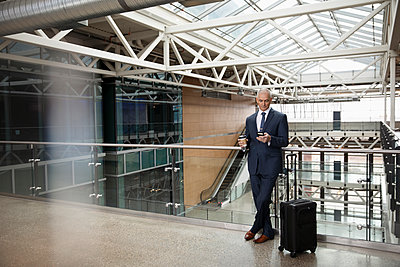 Senior businessman with suitcase and coffee using smart phone on office atrium balcony - p1192m2093719 by Hero Images