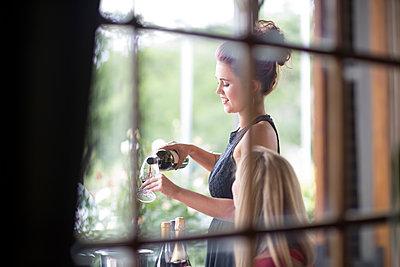 Waitress in restaurant serving red wine - p300m1156834 by zerocreatives