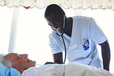 Happy male nurse examining senior man with stethoscope in hospital ward - p426m1494048 by Maskot