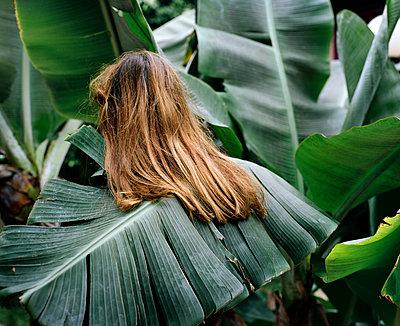 Teenager hidded in leaves - p453m2149759 by Mylène Blanc