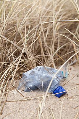 Plastikflasche im Sand - p993m823481 von Sara Foerster