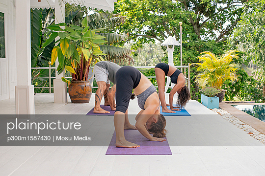 Two women and a man practicing yoga on terrace - p300m1587430 von Mosu Media