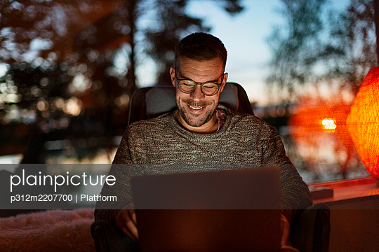 Man at home using laptop - p312m2207700 by Plattform
