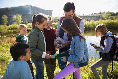 Science teacher and students conducting experiment field trip - p1192m1078411f by Hero Images