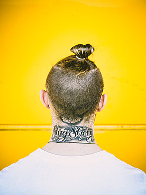 Man with pigtail and tattoo on his neck - p1267m2263409 by Jörg Meier