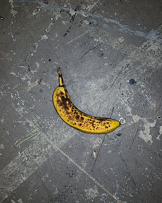 Banana on concrete floor - p1335m1492054 by Daniel Cullen