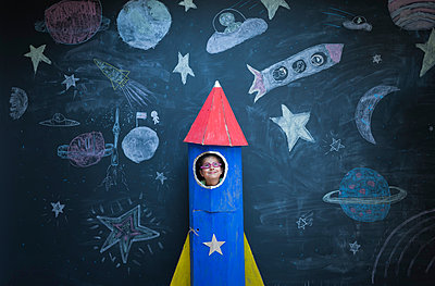 Portrait of girl in handmade space rocket in front of space themed chalk drawings - p429m1181021 by Ian Nolan