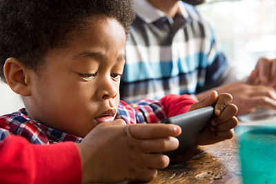 Mixed race boy using cell phone at table - p555m1312276 by Sam Diephuis