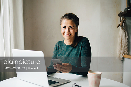 Portrait of smiling mid adult woman with mobile phone and laptop at table - p426m2138432 by Maskot