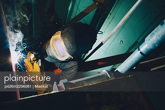 Young male welder worker using welding torch while working at site - p426m2296081 by Maskot