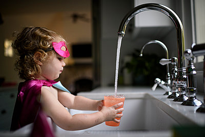 Side view of girl wearing superhero costume filling water in drinking glass while standing at home - p1166m2067549 by Cavan Images