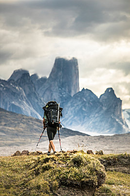 Backpacker hikes toward Mount Asgard in Akshayak Pass, Baffin Island - p1166m2190002 by Cavan Images
