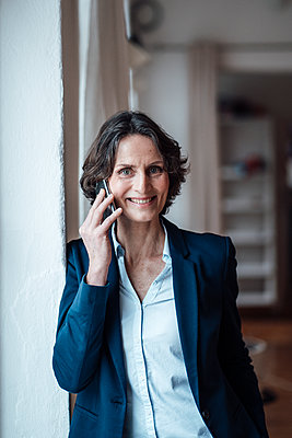 Smiling businesswoman talking on smart phone at home - p300m2267031 by Robijn Page
