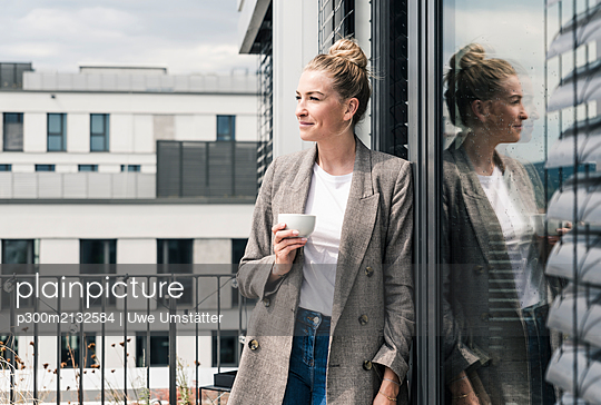 Businesswoman with coffee cup standing on roof terrace - p300m2132584 by Uwe Umstätter