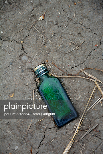 Green glass bottle trodden in soil, elevated view - p300m2213664 by Axel Ganguin