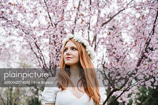 Beautiful woman wearing white flower tiara looking away - p300m2274020 by Eva Blanco