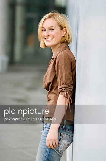 Happy young woman leaning against concrete wall