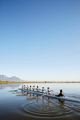 Female rowers rowing scull on tranquil lake under blue sky - p1023m1575854 by Richard Johnson