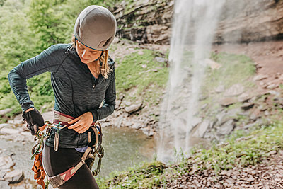 Woman puts gear back on harness after rappelling waterfall in NY - p1166m2084566 by Cavan Images