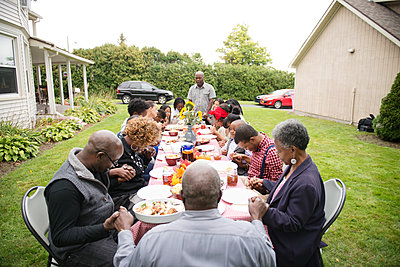 Family Members Praying Before a Meal at a Reunion - p1166m968657f by Cavan Images
