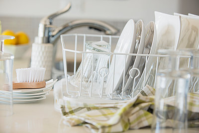 Modern white dishes drying in rack. - p1192m1132241f by Hero Images