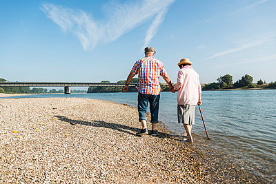 Germany, Ludwigshafen, back view of senior couple walking hand in hand at riverside - p300m1068967f by Uwe Umstätter