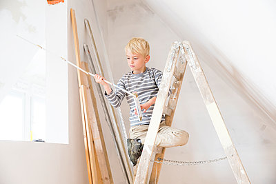 Boy with pocket rule on ladder in attic to be renovated - p300m2083639 by Michelle Fraikin