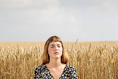 Portrait of young woman with eyes closed relaxing in front of grain field - p300m2131859 by FL photography