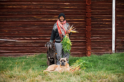 Woman with dogs and freshly picked carrots - p312m2080282 by Matilda Holmqvist