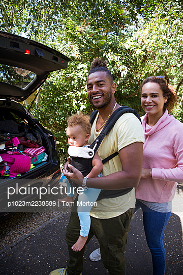 Portrait happy parents with toddler daughter outside car - p1023m2238589 by Tom Merton