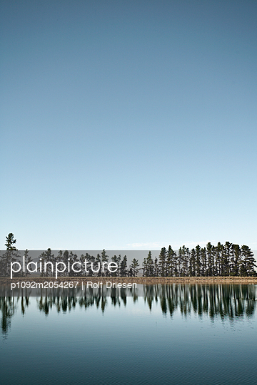 Lake with firs on the waterfront - p1092m2054267 by Rolf Driesen