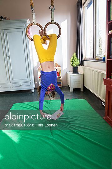 Mädchen hängt kopfüber und liest - p1231m2013518 von Iris Loonen
