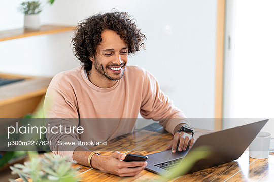 Smiling businessman holding smart phone while working on laptop at home - p300m2277621 by Steve Brookland