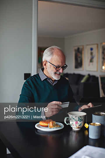 Smiling wrinkled man holding credit card while using digital tablet over table in living room - p426m2213221 by Maskot