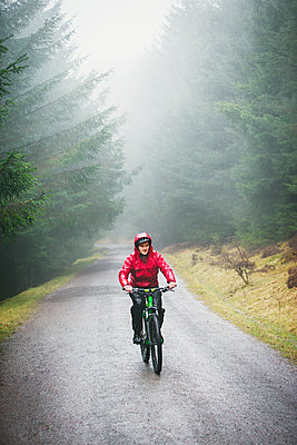 Man mountain biking in rain - p1023m2135879 by Robert Daly