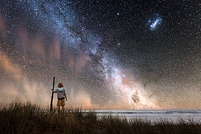 Boy holding walking stick standing at beach against starry sky - p1166m2129658 by Cavan Images