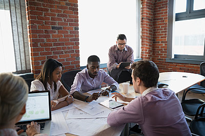 Business people discussing blueprints in conference room meeting - p1192m1085841f by Hero Images