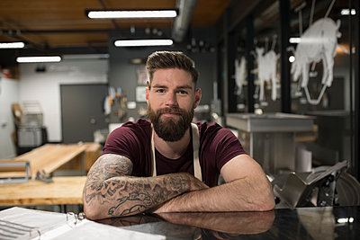 Portrait confident male butcher with tattoos and beard in butcher - p1192m1493363 by Hero Images