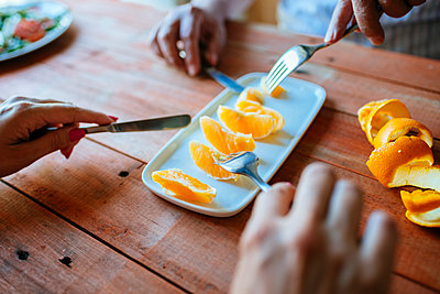 Hands of two persons eating orange slices with cutlery - p300m1166022 by Kiko Jimenez