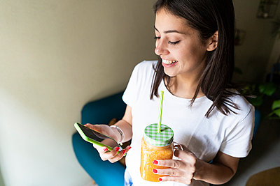 Happy young woman with a smoothie using cell phone in a cafe - p300m2140398 by Giorgio Fochesato